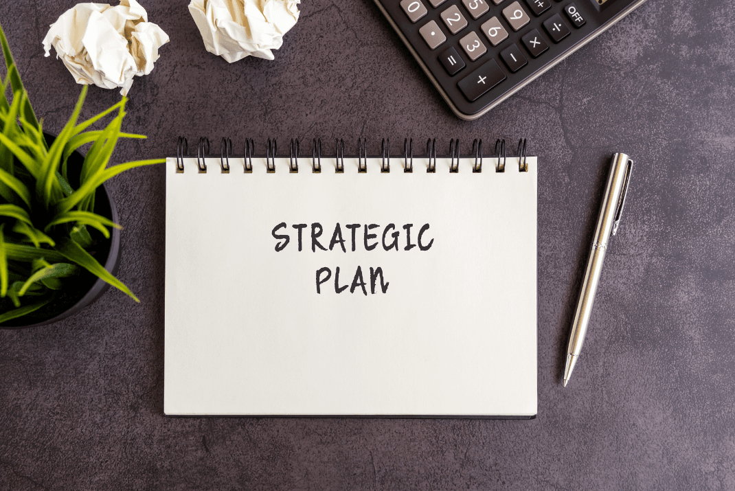 Strategic Plan document on a desk with accessories around it.